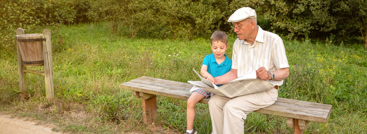 elderly man reading newspaper with young boy